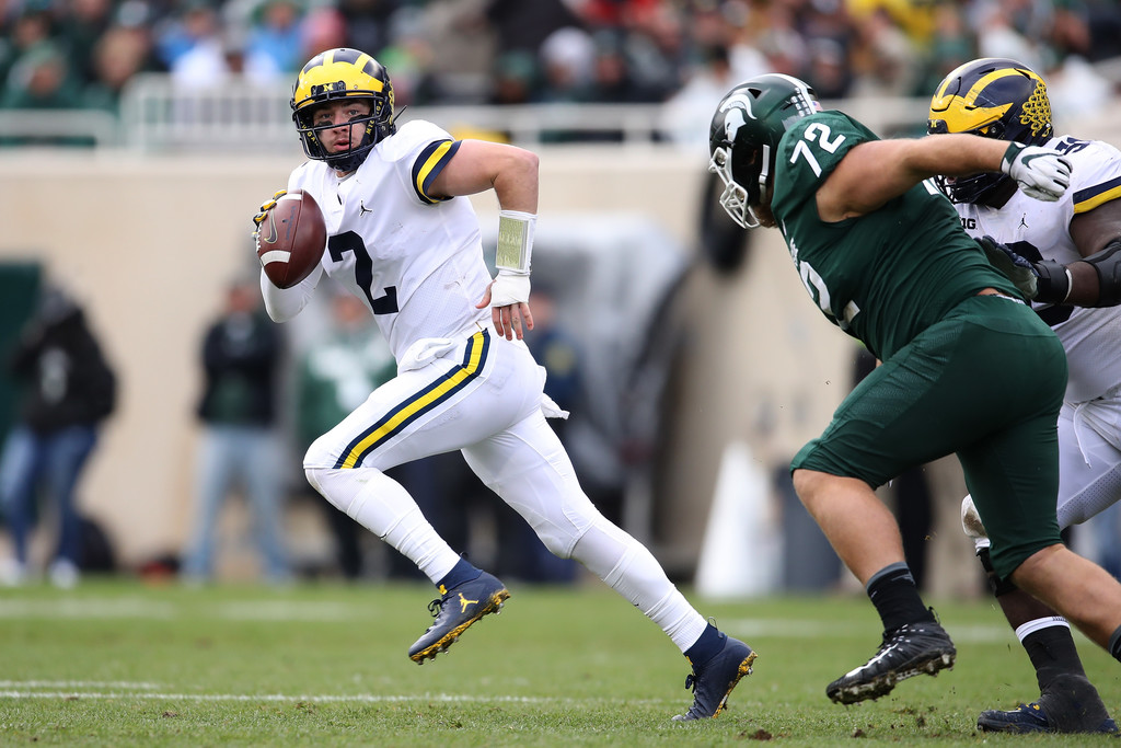 Michigan Wolverines quarterback Shea Patterson looks for an open receiver while being chased by Mike Panasluk against the Michigan State Spartans