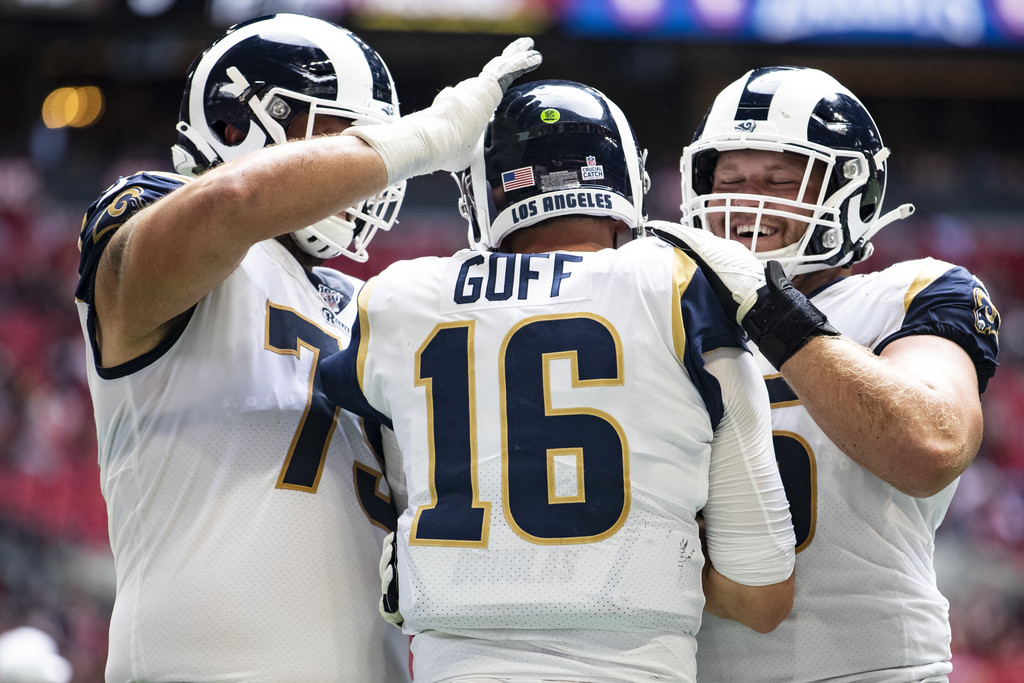 Los Angeles Rams center Brian Allen and tackle Rob Havenstein celebrate with Jared Goff after he scored on a rushing touchdown against the Atlanta Falcons