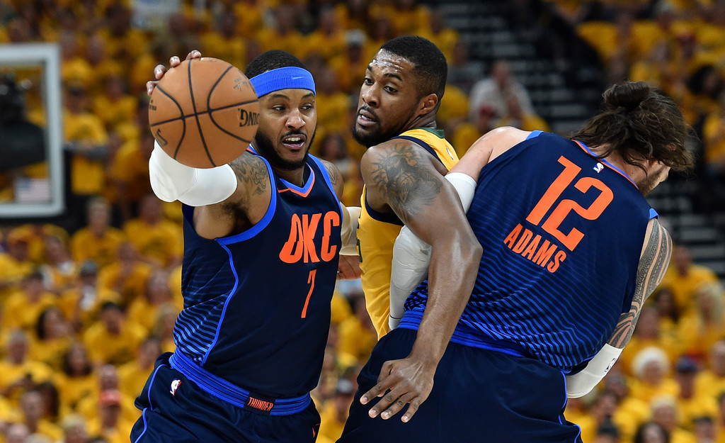 Former Oklahoma City Thunder forward Carmelo Anthony drives past Derrick Favors against the Utah Jazz