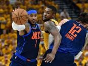 Former Oklahoma City Thunder forward Carmelo Anthony drives past Derrick Favors against the Utah Jazz