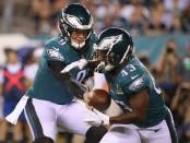 Former Philadelphia Eagles quarterback Nick Foles hands the ball off to Darren Sproles against the Atlanta Falcons