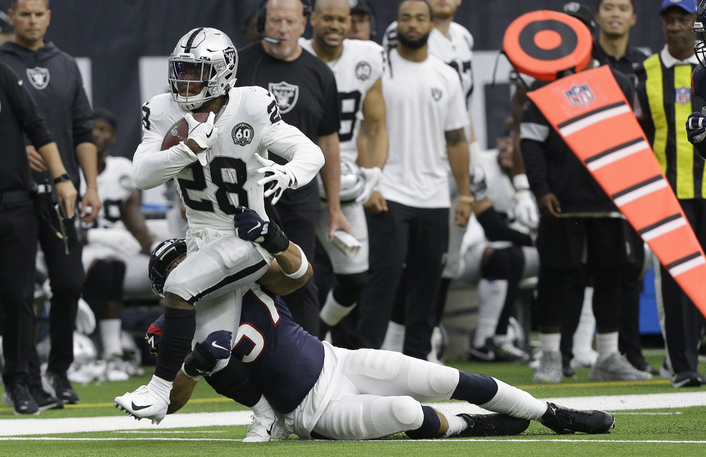 Houston Texans linebacker Dylan Cole attempts to tackle Josh Jacobs against the Oakland Raiders