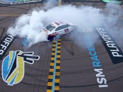 Joe Gibbs Racing driver Denny Hamlin celebrates with a burnout after winning the Bluegreen Vacations 500