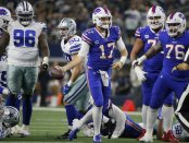 Buffalo Bills quarterback Josh Allen celebrates after recovering a fumbled nap and getting a first down against the Dallas Cowboys