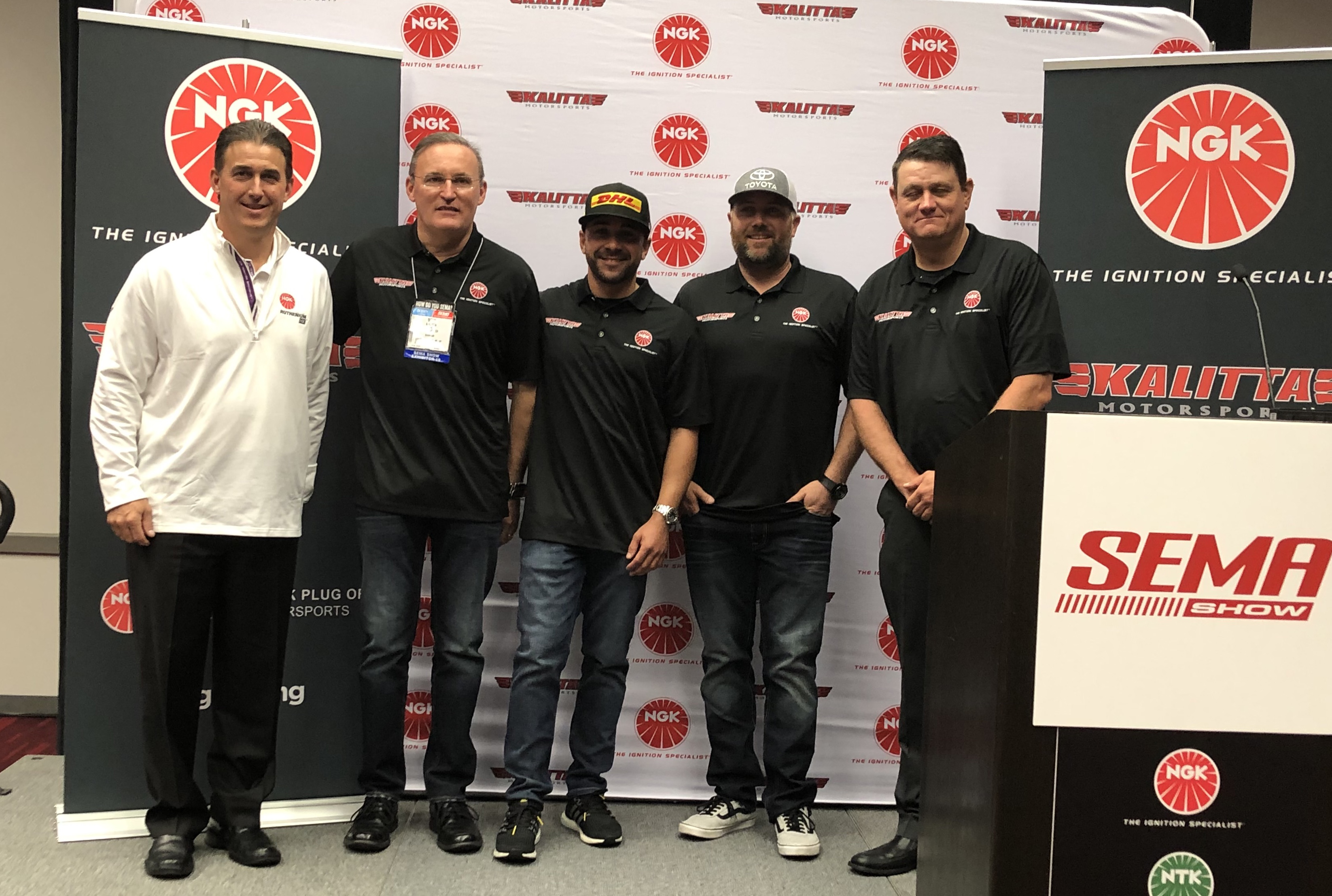 NGK Vice President of Aftermarket Brian Norko, Kalitta Motorsports GM Chad Head, and team Doug Kalitta, J.R. Todd, Shawn Langdon at NGK Spark Plugs,,Kalitta Motorsports sponsorship announcement during SEMA