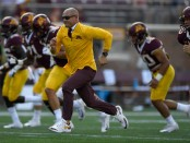 Minnesota Golden Gophers head coach P.J. Fleck runs onto the field with his players during warm ups before the game against the Miami (Ohio) RedHawks