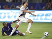 Los Angeles Galaxy star Zlatan Ibrahimović battles for control ball against Chris Schuler against the Orlando City SC