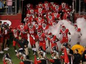 Former Rutgers Scarlet Knights head coach Greg Schiano leading his team onto the field to play the Connecticut Huskies