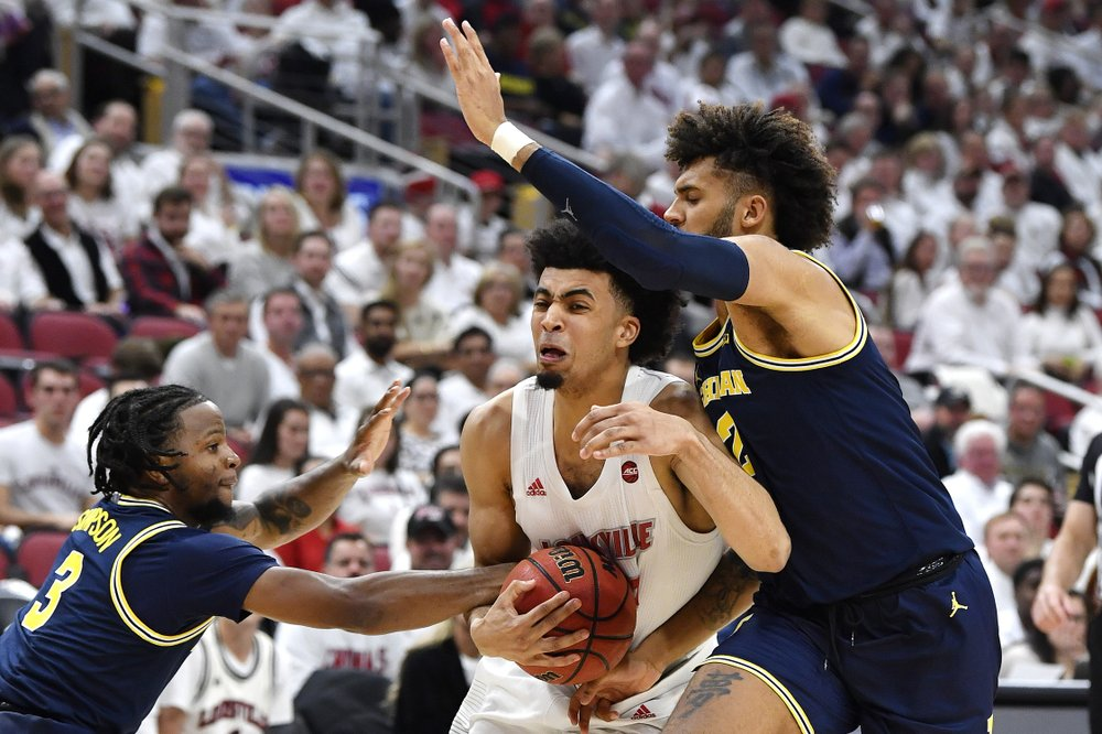 Louisville Cardinals forward Jordan Nwora is fouled by guard Zavier Simpson against the Michigan Wolverines