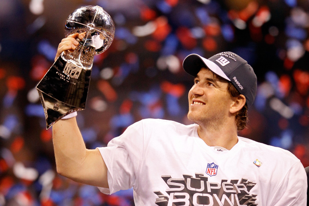Former New York Giants quarterback Eli Manning poses with the Vince Lombardi Trophy after defeating the New England Patriots, 21-17, in Super Bowl XLVI