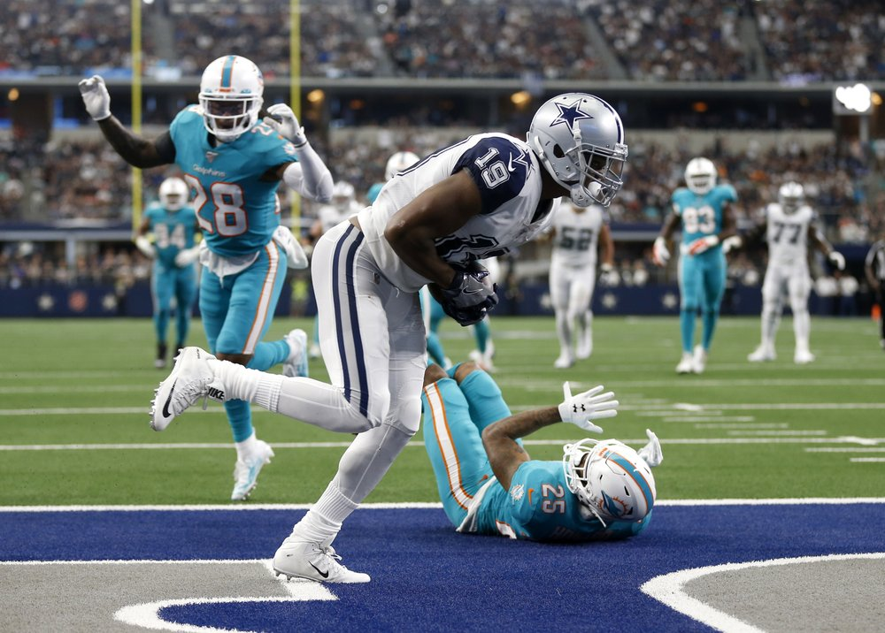 Dallas Cowboys wide receiver Amari Cooper catches a pass for a touchdown in front of Xavien Howard and Bobby McCain against the Miami Dolphins