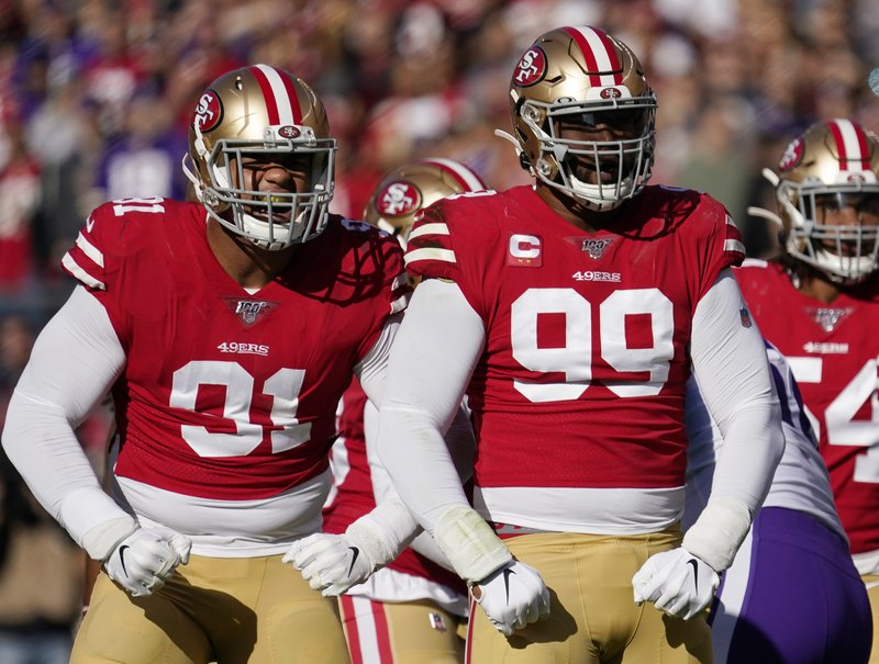 Former San Francisco 49ers defensive lineman DeForest Buckener celebrates after a play with former teammate Arik Armstead against the Minnesota Vikings during the first half in their NFL Divisional playoff game