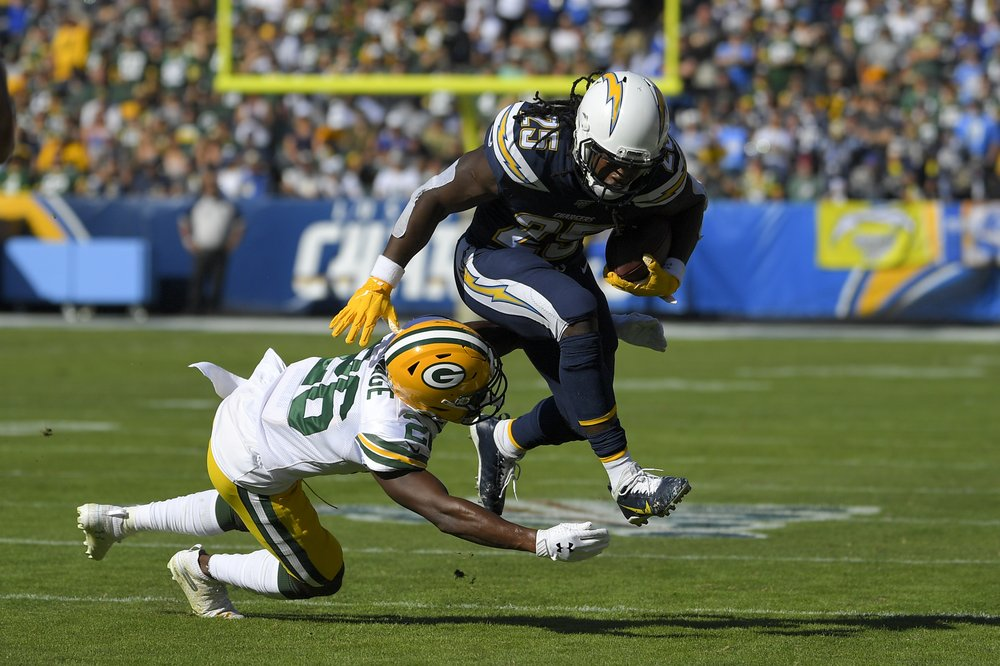 Former Los Angeles Chargers running back Melvin Gordon III runs over Darnell Savage against the Green Bay Packers