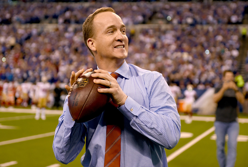 Former NFL quarterback Peyton Manning throws a ceremonial pass to former teammate Marvin Harris during Manning number retirement ceremony during halftime between the Indianapolis Colts and the San Francisco 49ers