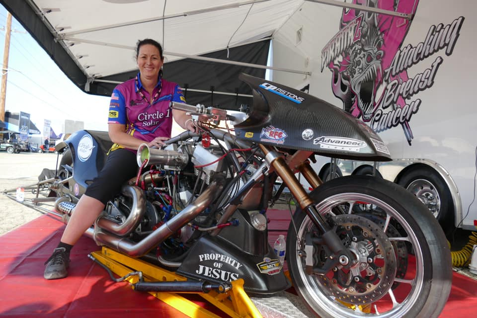 Nitro drag racer Janette Thornley on a Top Fuel Harley at an event in the pit area