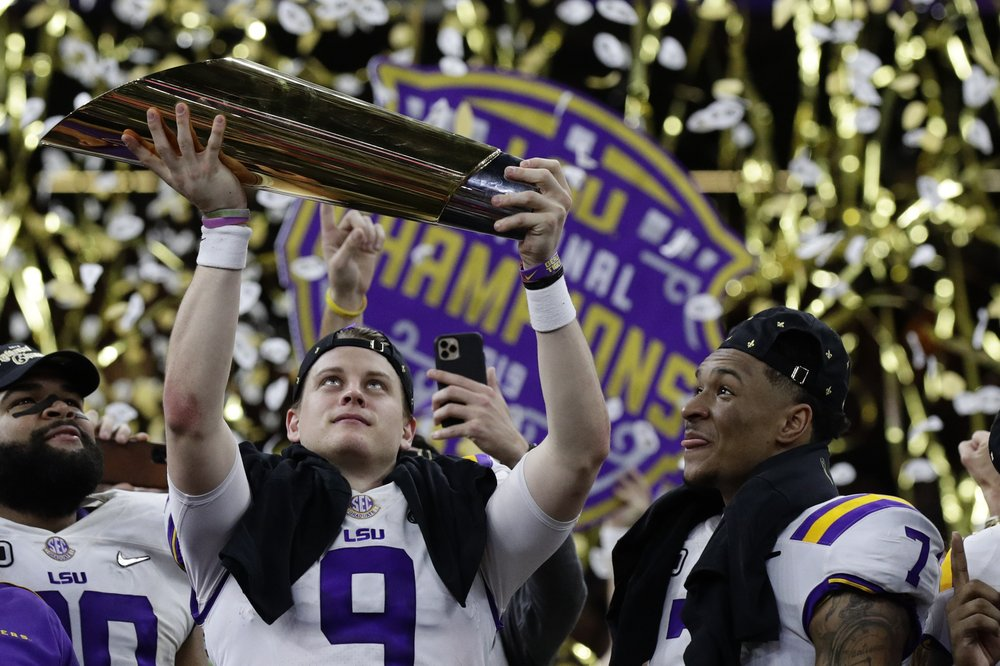 Former LSU Tigers quarterback Joe Burrow lifts the College Football Playoff National Championship trophy after his Tigers team defeated the Clemson Tigers