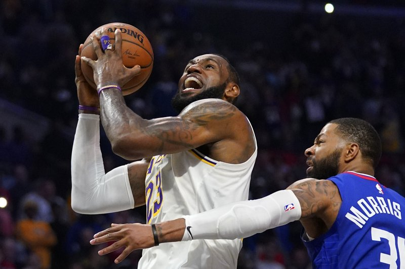 Los Angeles Lakers point guard LeBron James shoots as Marcus Morris Sr. defends his shot against the Los Angeles Clippers