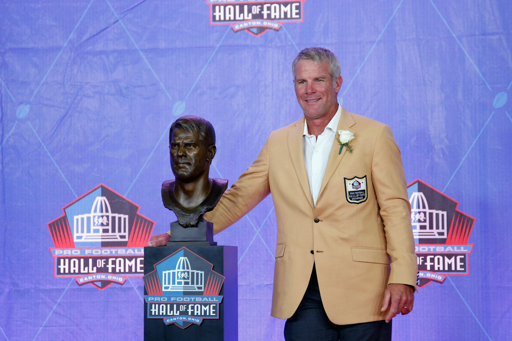 Former NFL quarterback Brett Favre poses with a bronze bust during the NFL Hall of Fame Enshrinement Ceremony