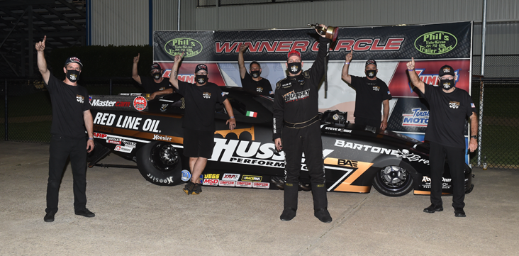 Top Alcohol Funny Car pilot Sean Bellemeur hoists the Wally after winning the Keurig Dr. Pepper Lone Star Nationals presented by Driven Automotive Protection