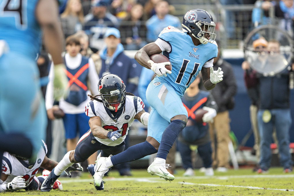 Tennessee Titans wide receiver A.J. Brown catches a pass and avoids a tackle by Bradley Roby against the Houston Texans
