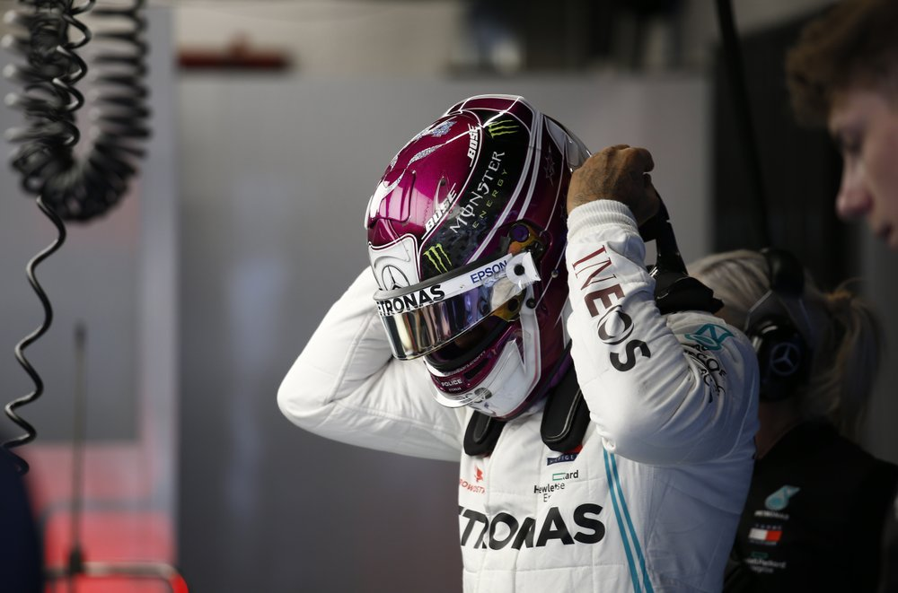Mercedes-AMG Petronas F1 driver Lewis Hamilton adjusts his helmet in the pit lane during the Formula One pre-season testing session