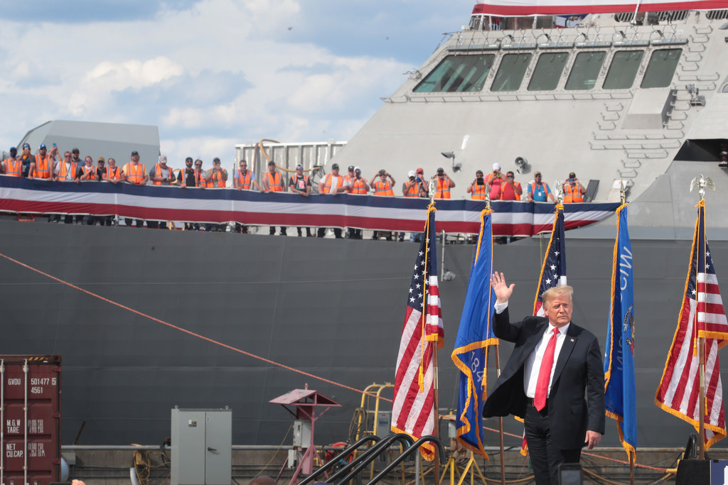 United States President Donald Trump waves after speaking to guests during a visit to the Fincantieri Marinette Marine shipyard