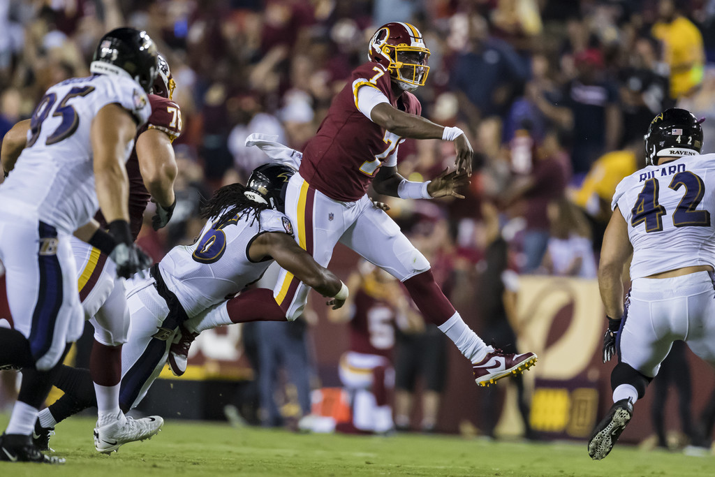 Washington Redskins quarterback Dwayne Haskins is hit by Tim Williams after attempting a pass against the Baltimore Ravens