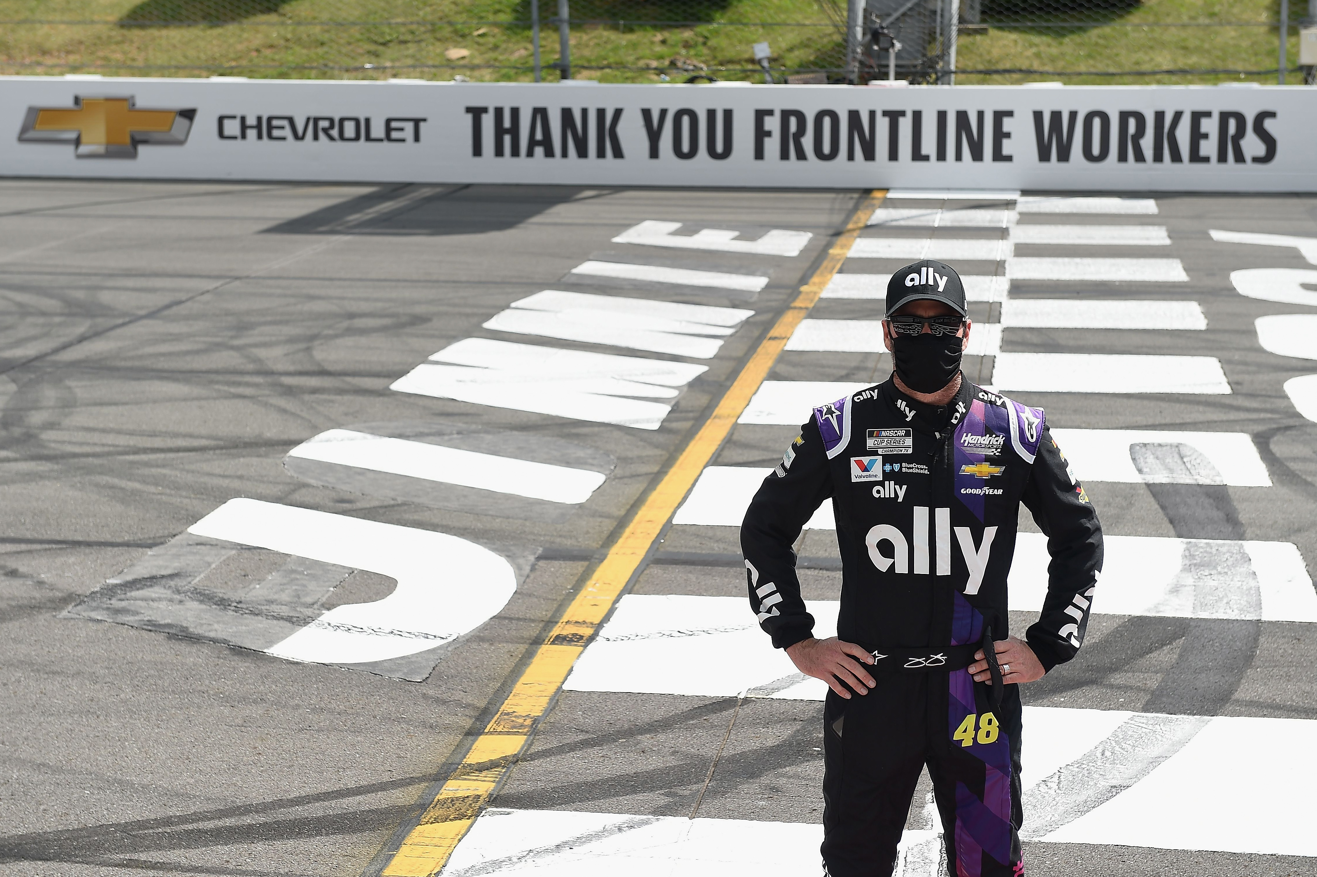 Ally Chevrolet driver Jimmie Johnson poses on the Start/Finish line to show support for front line workers prior to the NASCAR Cup Series Pocono 350