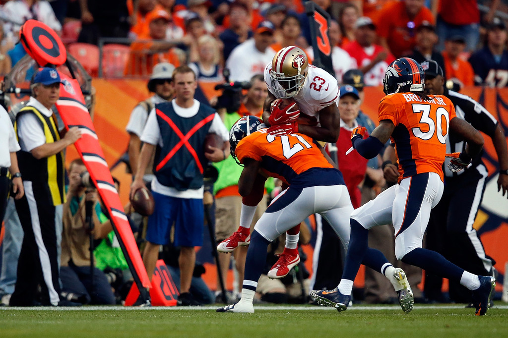 Former San Francisco 49ers running back Reggie Bush is tackled by Aqib Talib against the Denver Broncos