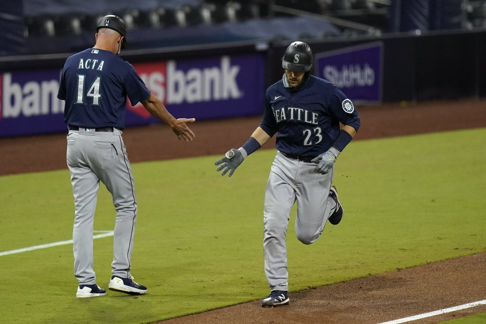 Former Seattle Mariners catcher/infielder Aaron Nola reacts with third base coach Manny Acta after hitting a home run against the San Diego Padres