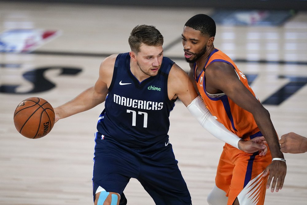 Dallas Mavericks guard Luka Dončić looks to drive against Phoenix Suns forward Mikal Bridges during the first half of their NBA game