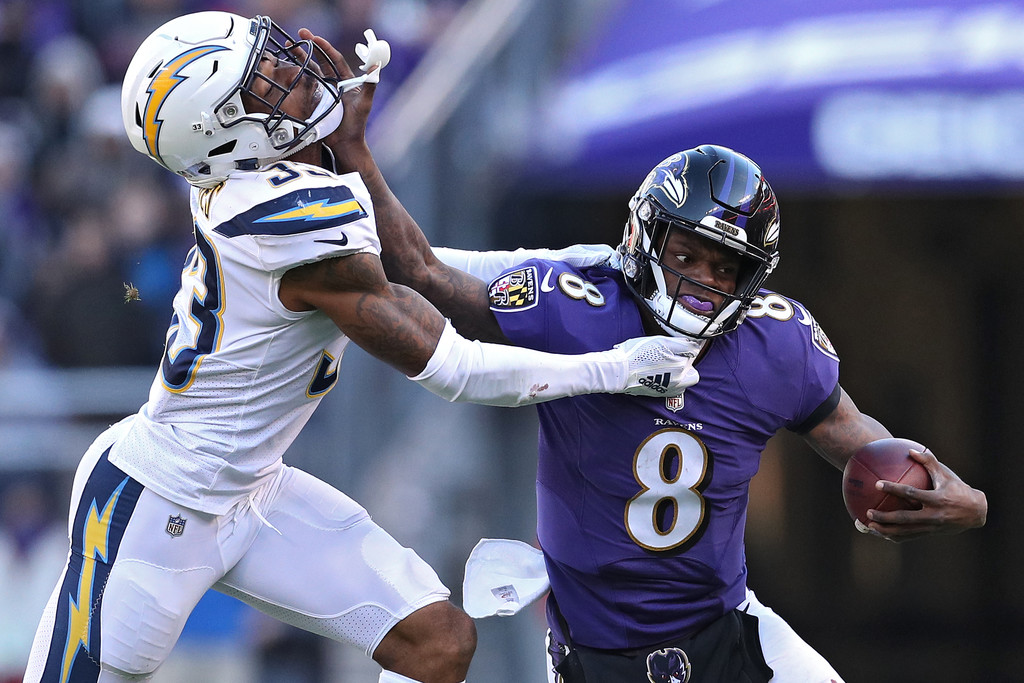 Baltimore Ravens quarterback Lamar Jackson stiff arms Derwin James against the Los Angeles Chargers during the AFC Wild Card Playoff game
