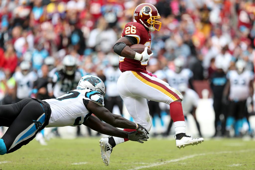 Former Washington Redskins running back Adrian Peterson runs past Mario Addison against the Carolina Panthers
