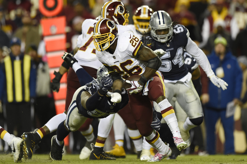 Former Washington Redskins running back Adrian Peterson breaks a tackle by David Irving against the Dallas Cowboys