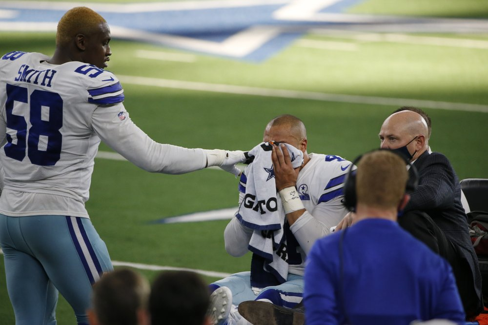 Dallas Cowboys defensive end Aldon Smith comforts quarterback Dak Prescott as he is carted off the field after suffering a lower right leg injury running the ball against the New York Giants