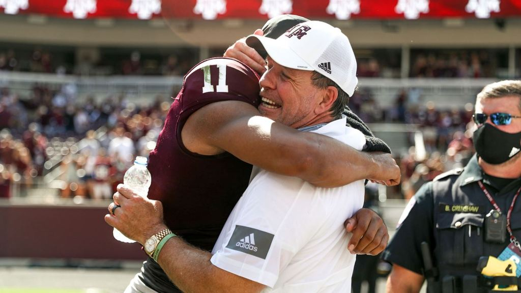 Texas A&M Aggies quarterback Kellen Mond and head coach Jimbo Fisher hug after the big win over the Florida Gators