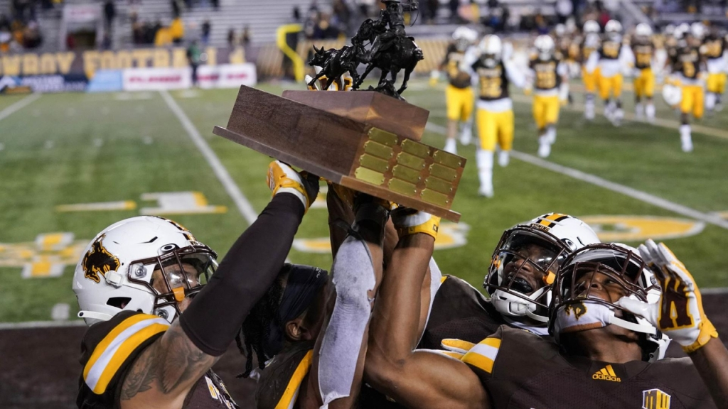Wyoming Cowboys celebrates with the Paniolo Trophy following a 31-7 win over the Hawai'i Rainbow Warriors