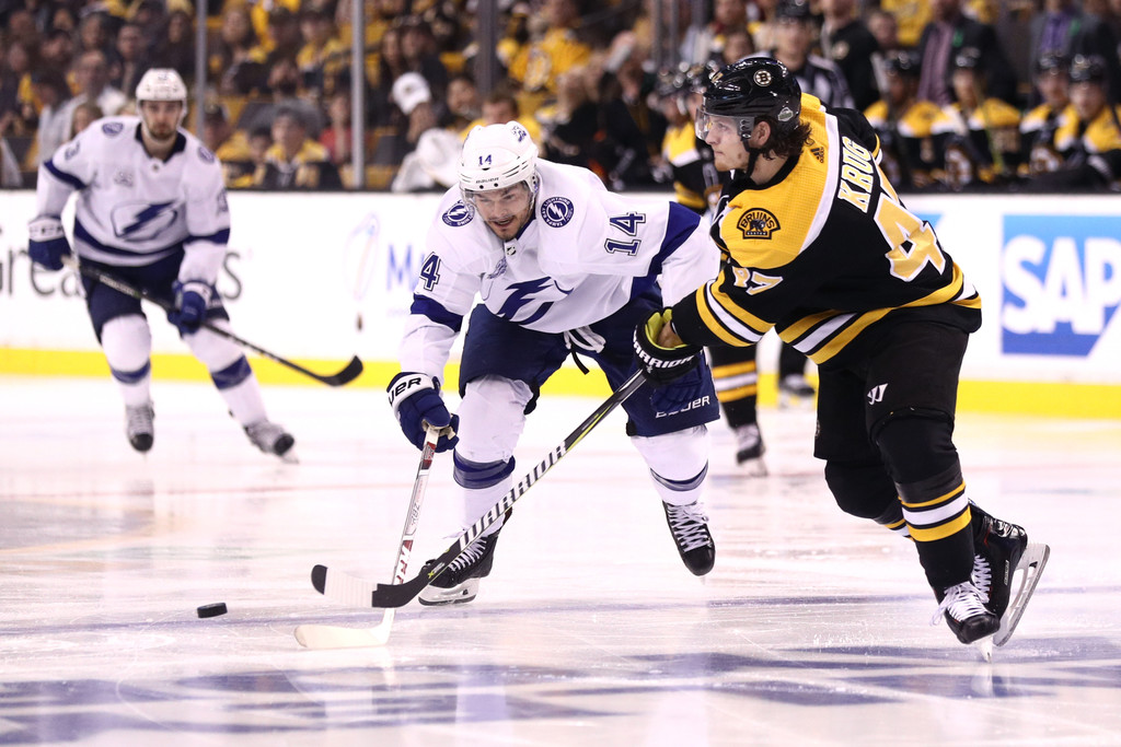 Former Boston Bruins defenseman Torey Krug and Tampa Bay Lightning player Chris Kunitz compete for control of the puck during Game Three of the Eastern Conference Second Round during the 2018 NHL Stanley Cup Playoffs