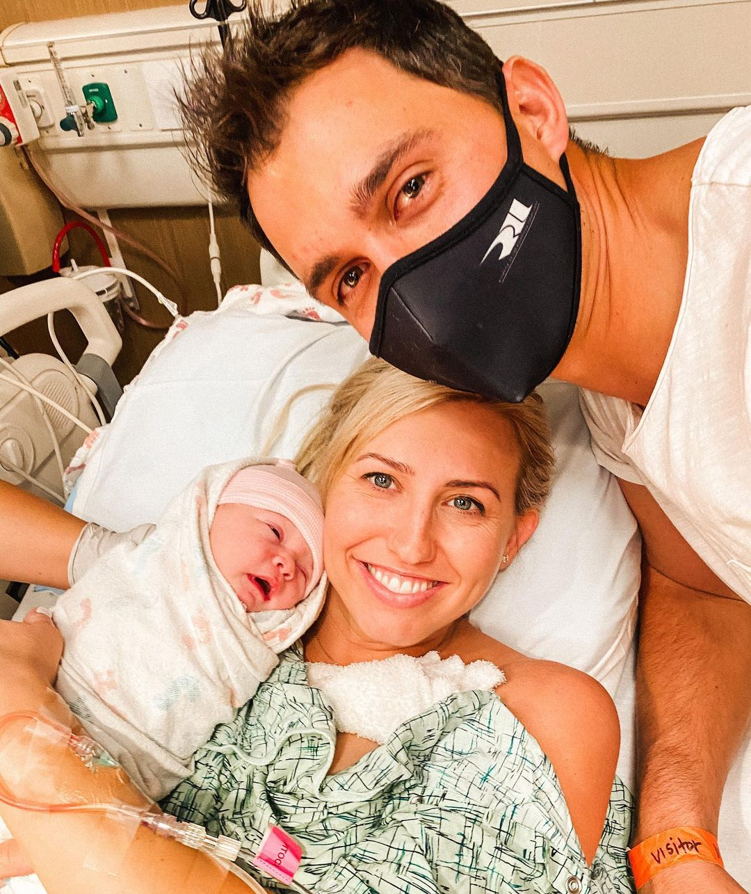 Former John Force Racing Funny Car pilot Courtney Force holding her new daughter Harlan Rahal with her IndyCar driver Graham Rahal looking over the two women