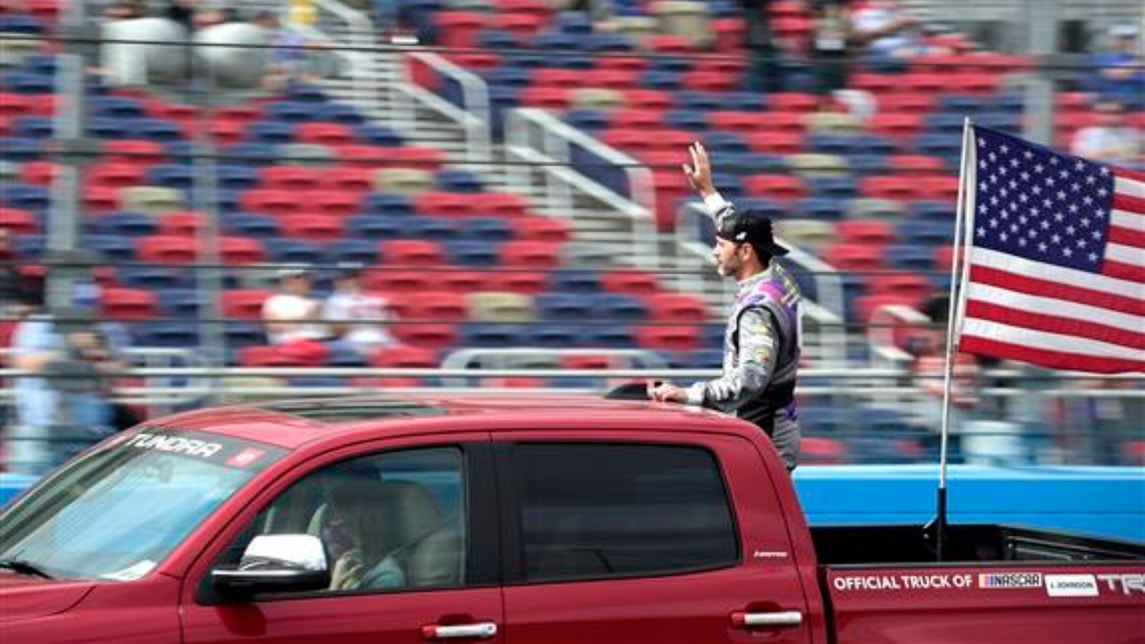 Ally Chevrolet driver Jimmie Johnson waves to fans as he is driven on the track during pre-race ceremonies prior to the NASCAR Cup Series Season Finale 500