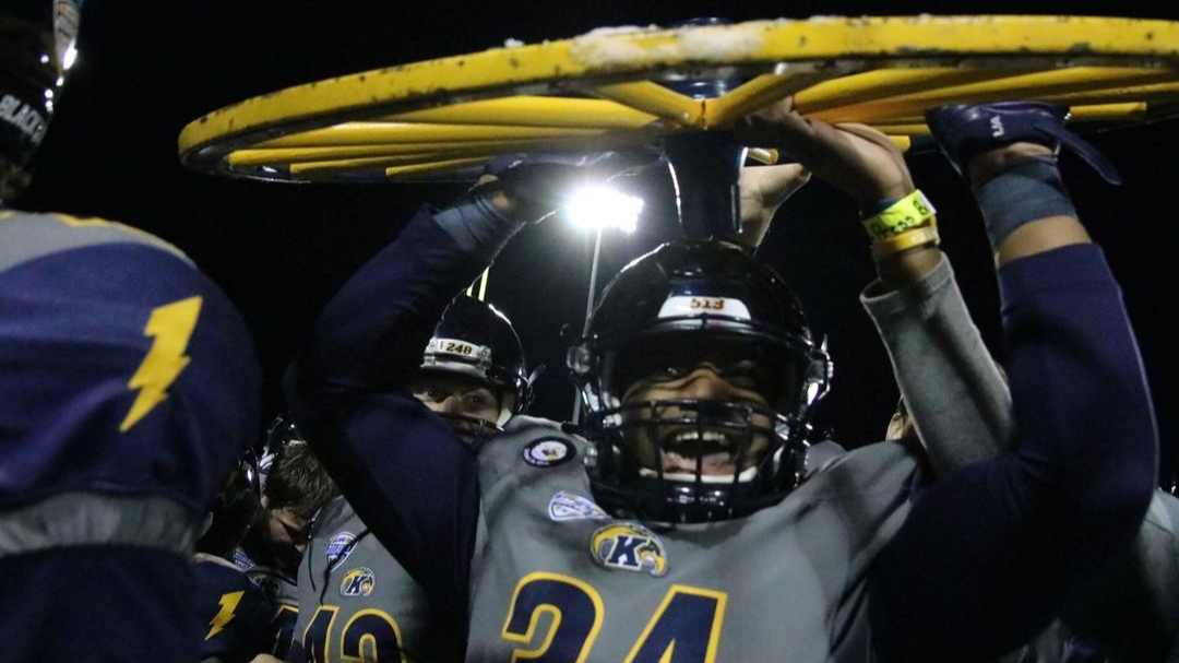 Kent State Golden Flashes football players celebrate with the wheel after their big win over the Akron Zips