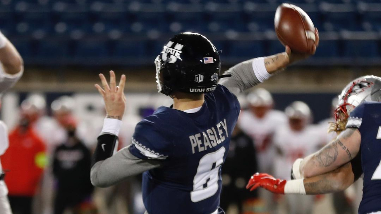 Utah State Aggies quarterback Andrew Peasley attempts to throw a pass against the New Mexico Lobos