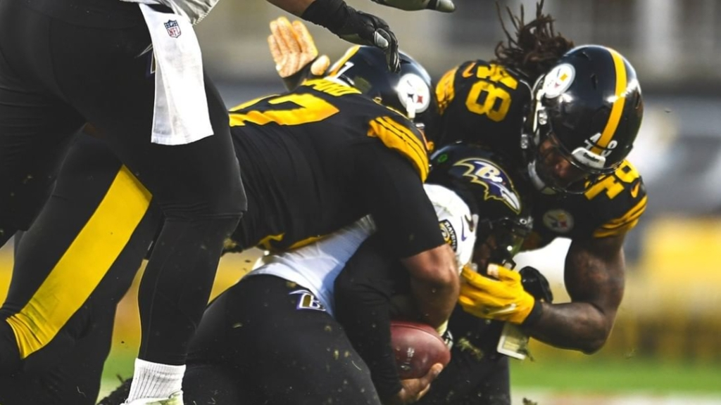 Pittsburgh Steelers linebacker Bud Dupree and his teammate tackles a Baltimore Ravens player