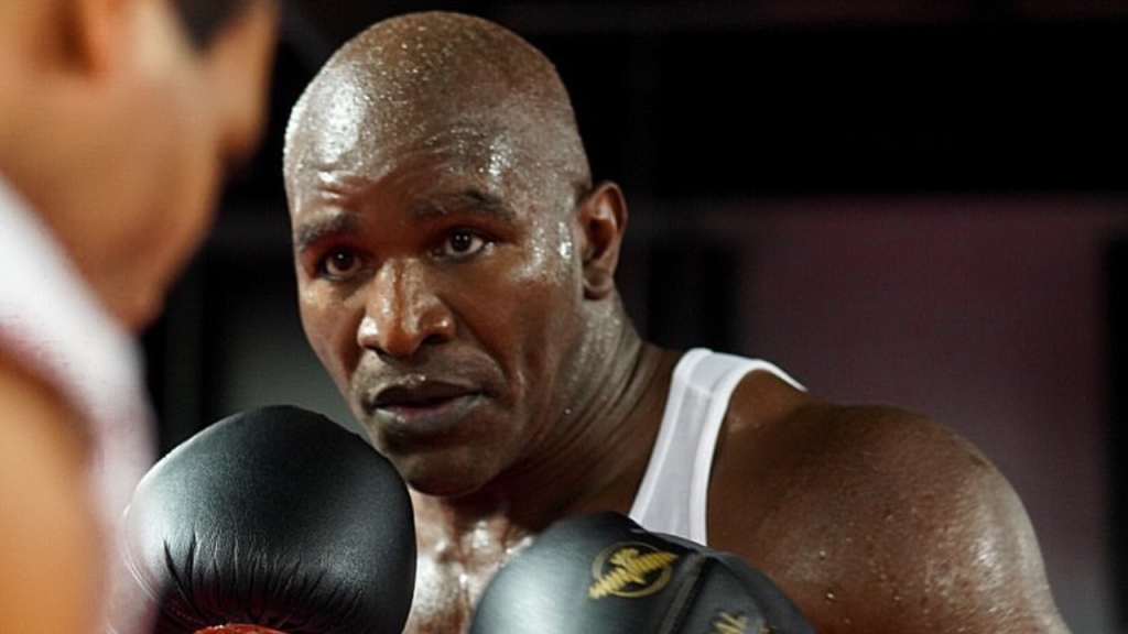 Boxing legend Evander Holyfield is in the gym training with an unnamed trainer