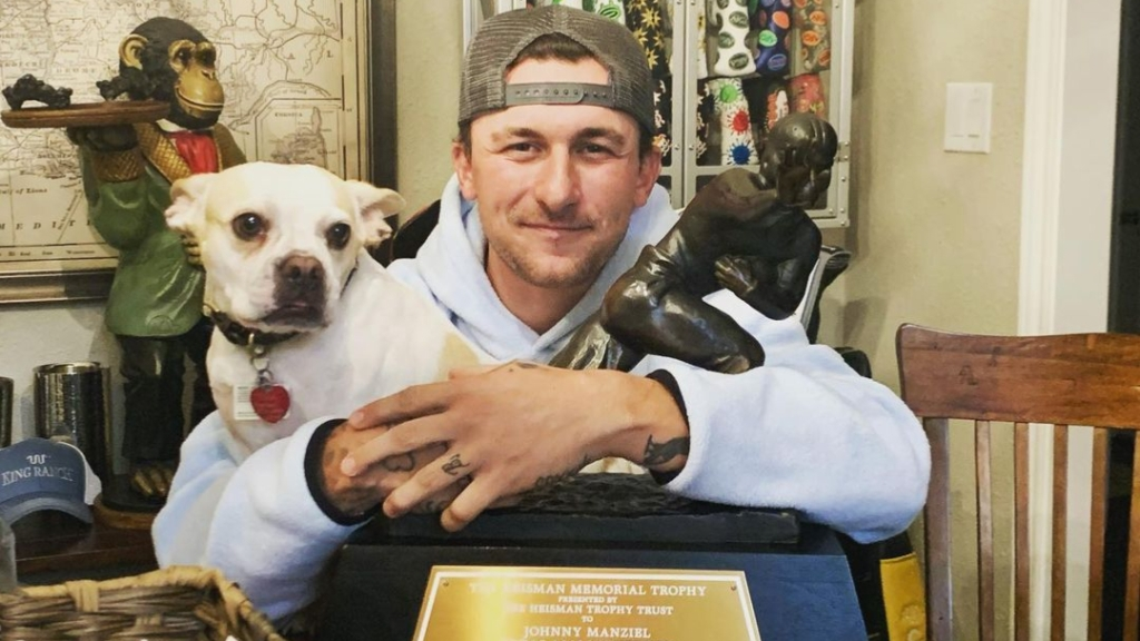 Former NFL quarterback Johnny Manziel holds his dog and his 2012 Heisman Trophy