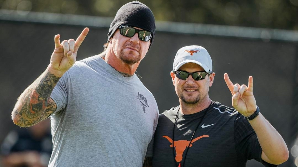 Former Texas Longhorns head coach Tom Herman stands next to The Undertaker Mark Calaway