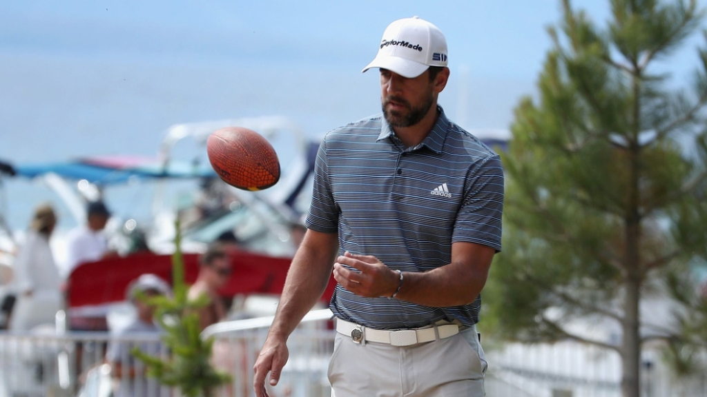 Green Bay Packers quarterback Aaron Rodgers catches a football thrown to him from fans on the beach at the American Century Championship