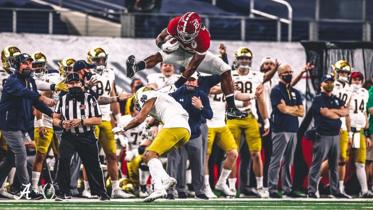 Alabama Crimson Tide running back Najee Harris hurdles over a Notre Dame Fighting Irish defensive player in the Rose Bowl Game presented by Capital One