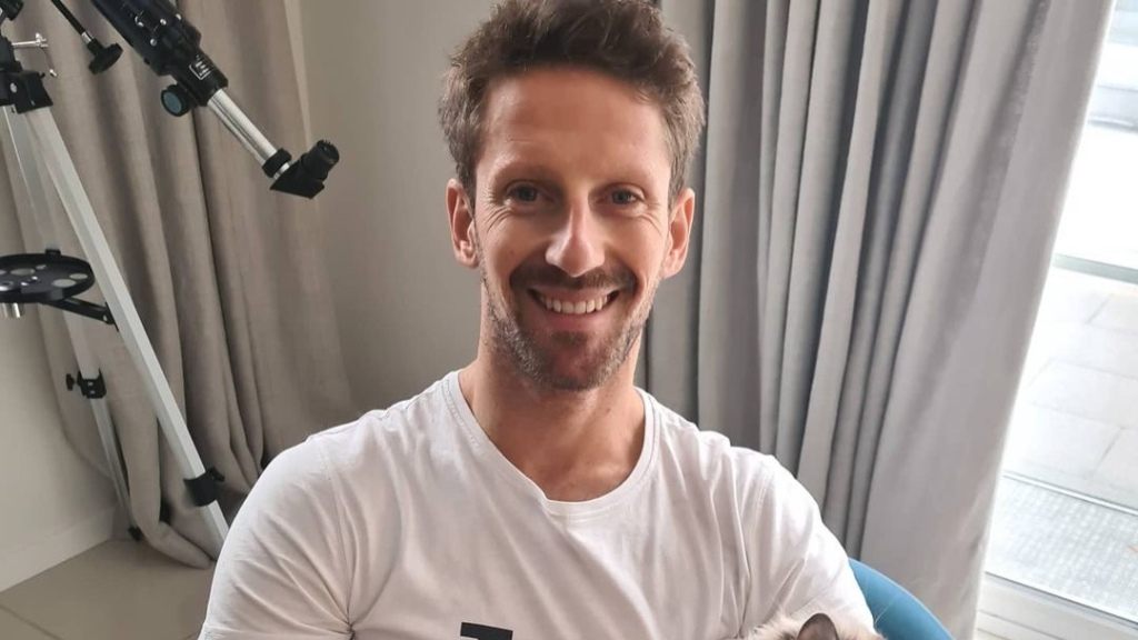 Former Formula One driver Romain Grosjean smiles while he pets an animal with his burned hands