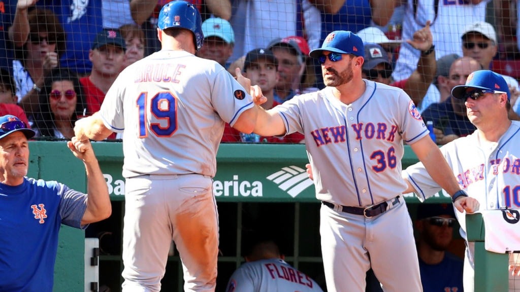 Former New York Mets manager Mickey Callaway congratulates Jay Bruce as he returns to the dugout after scoring against the Boston Red Sox